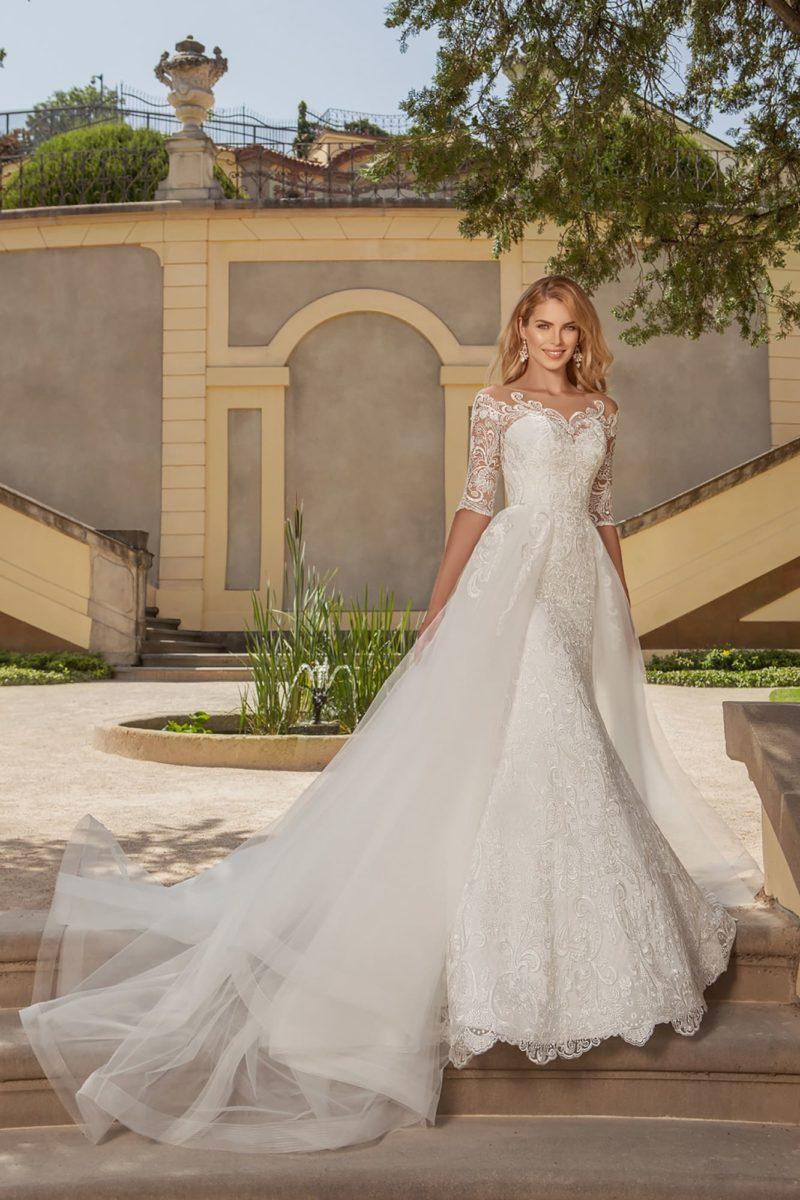 Роскошное свадебное платье с фигурным открытым лифом и многослойной юбкой с длинным шлейфом.