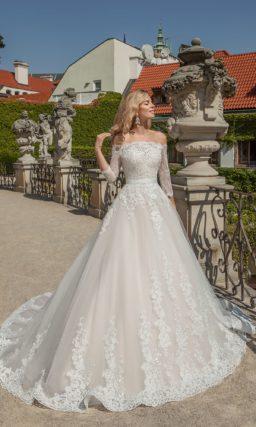 Пышное свадебное платье с портретным декольте, широким поясом на талии и кружевным декором.