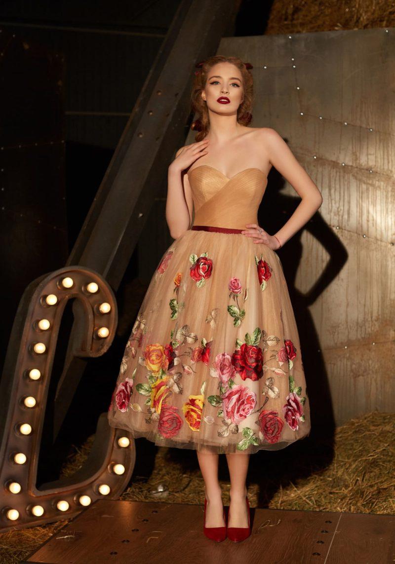 Золотистое вечернее платье с открытым лифом, ярким поясом и цветочной вышивкой на юбке.