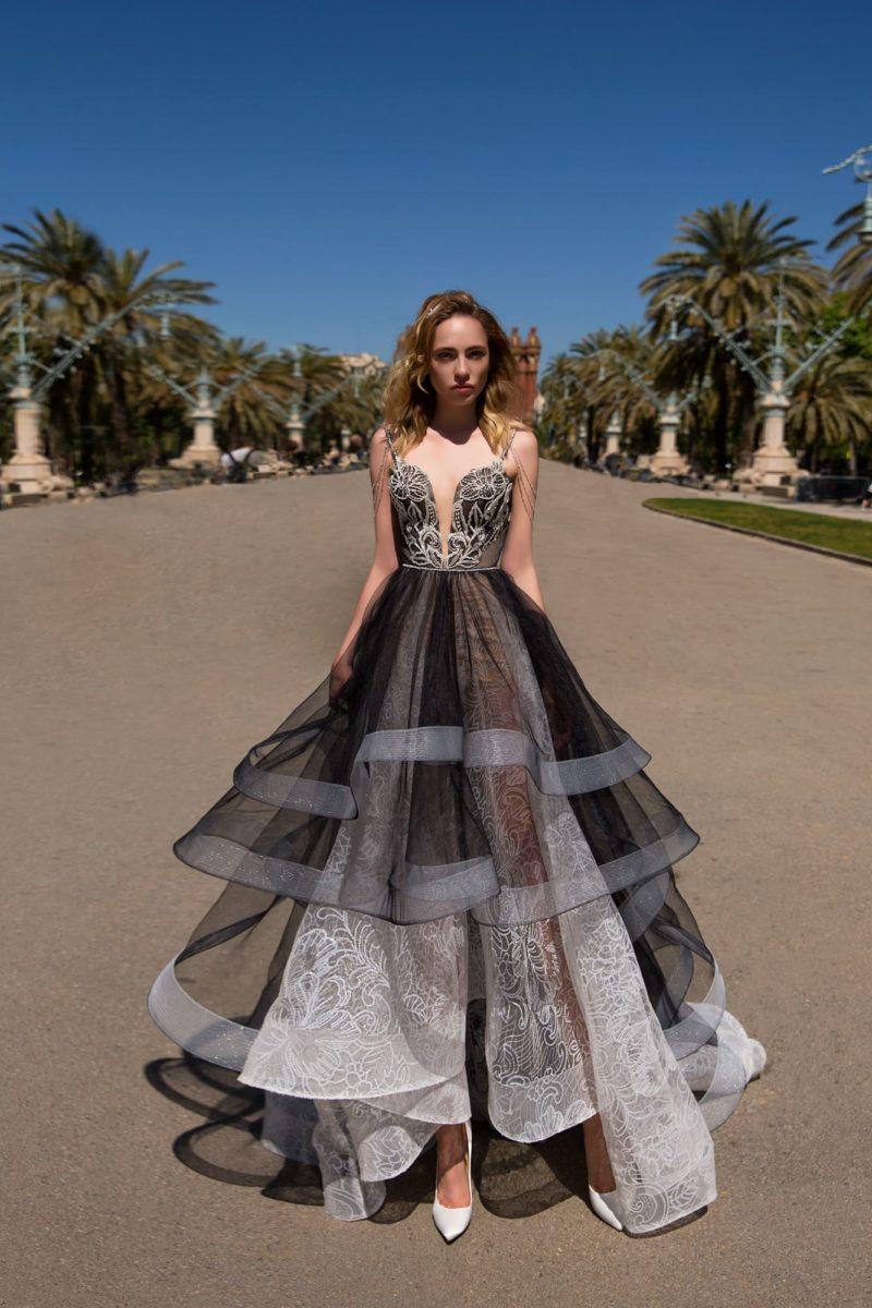 Пышное вечернее платье с многоярусной юбкой и кружевом, выполненное в черно-белых тонах.