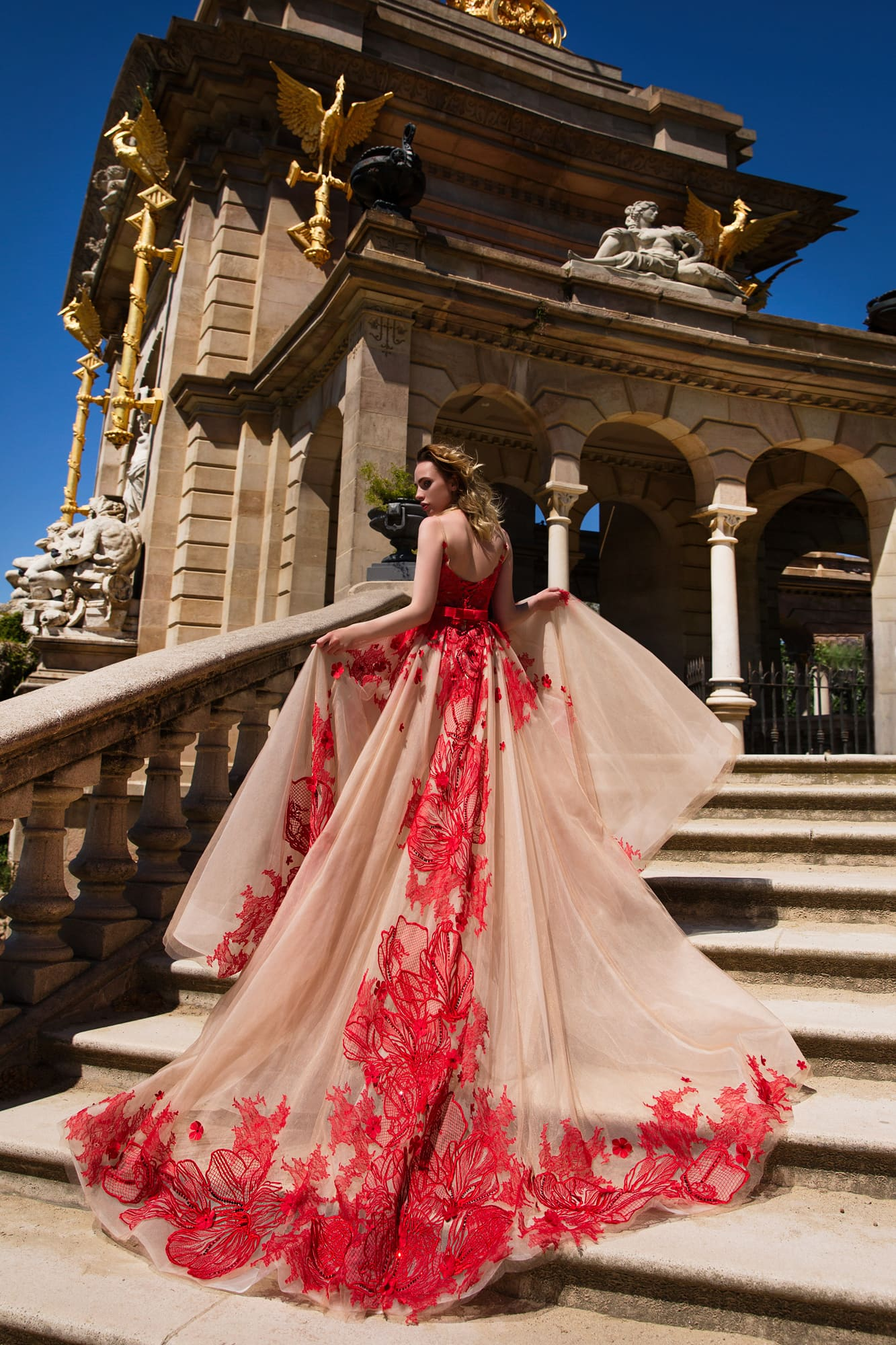 Бежевое вечернее платье с крупной красной отделкой из кружева и длинным многослойным шлейфом.