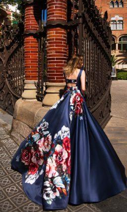 Темно-синее вечернее платье с изящным вырезом «лодочка» и цветочным рисунком по подолу.