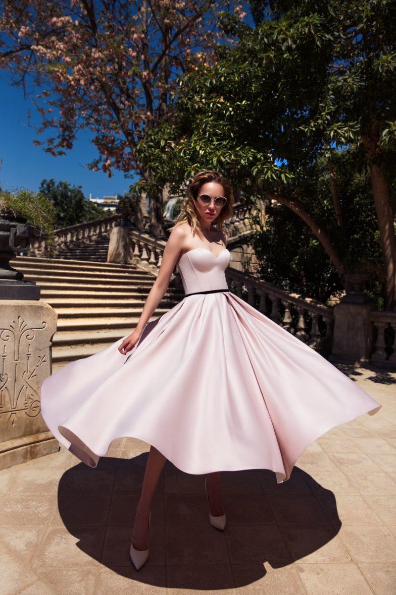 Розовое вечернее платье в стиле ретро, с открытым лифом, узким черным поясом и юбкой длины миди.