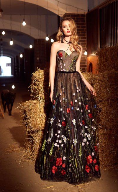 Впечатляющее вечернее платье с открытым верхом и яркой цветочной вышивкой по черной ткани.