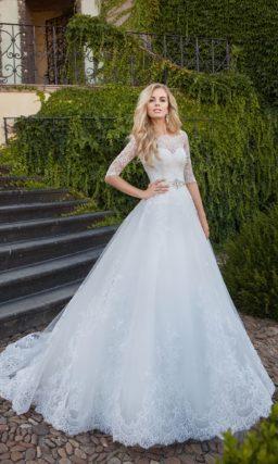 Закрытое свадебное платье, украшенное кружевом по низу подола.