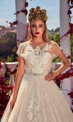 Пышное свадебное платье кремового цвета с белой кружевной отделкой и короткими рукавами.