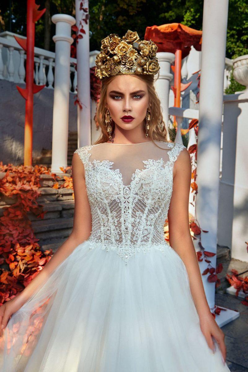 Элегантное свадебное платье с многослойным подолом и полупрозрачным вышитым корсетом.