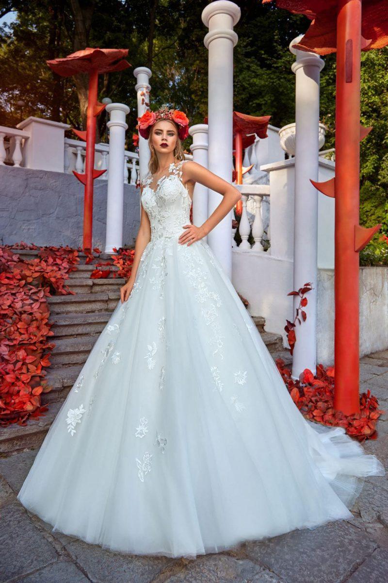 Белоснежное свадебное платье с глянцевыми цветочными аппликациями и небольшим шлейфом.