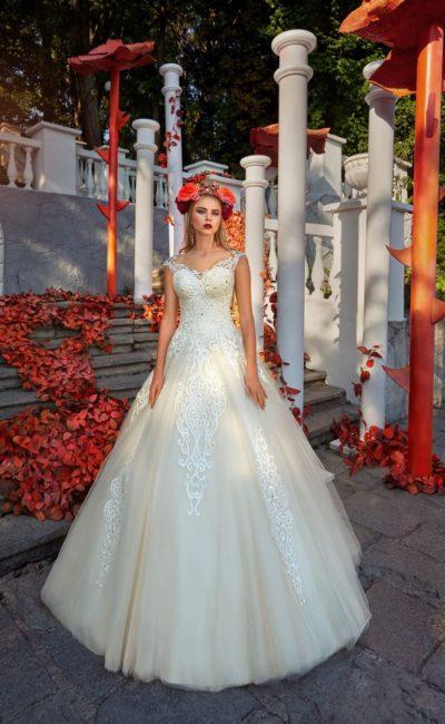 Пышное свадебное платье с легким кремовым оттенком, украшенное стильным белым кружевом.