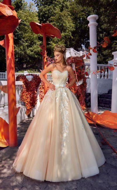 Открытое свадебное платье кремового оттенка, украшенное аппликациями и вышивкой.