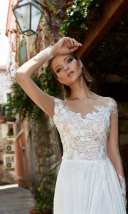 Нежное свадебное платье прямого кроя с прозрачным рукавом и разрезом по подолу юбки.