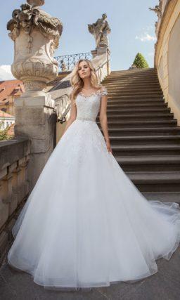 Пышное свадебное платье с кружевной отделкой корсета и романтичным многослойным шлейфом.