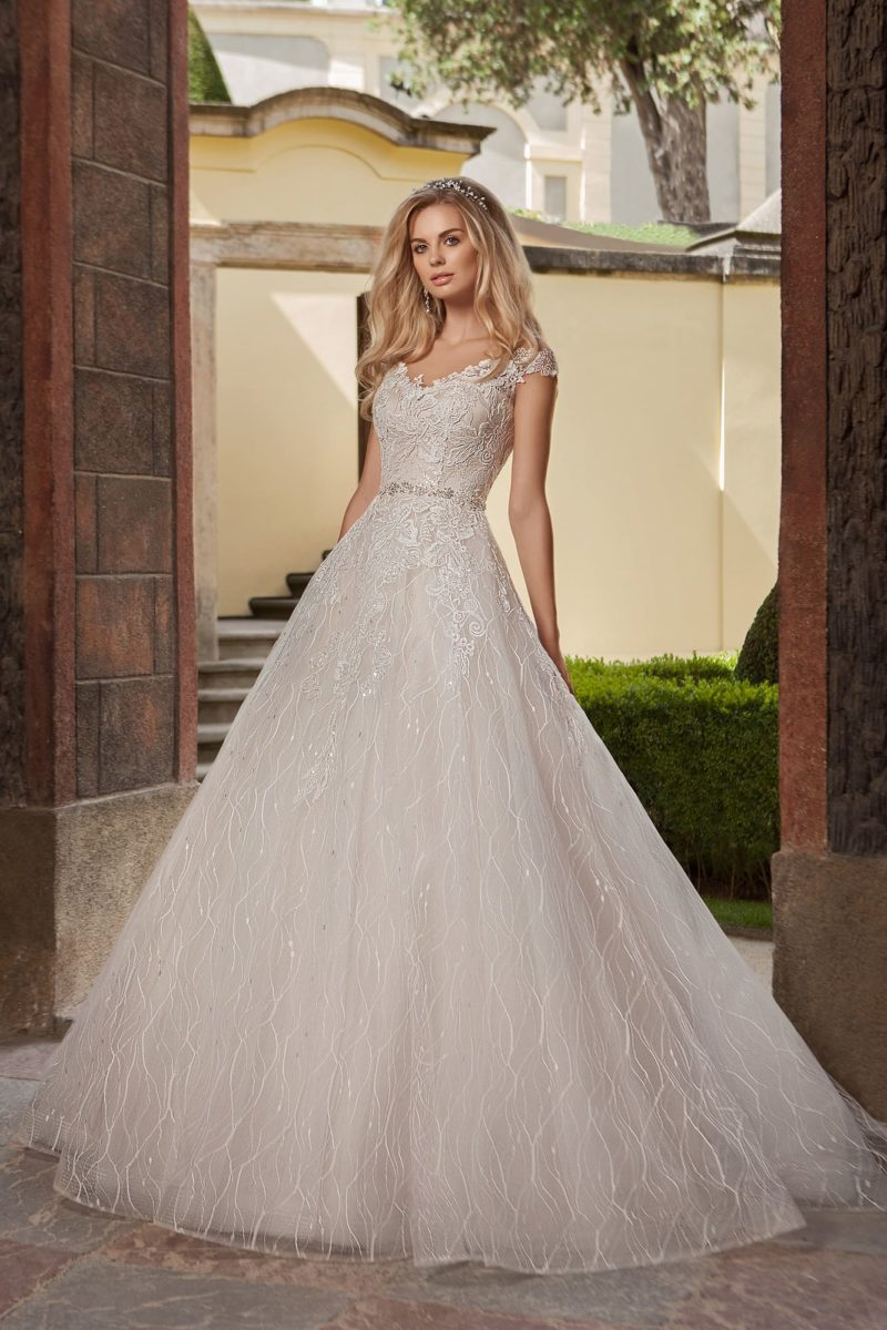 Фактурное свадебное платье кремового оттенка с элегантным декольте и юбкой силуэта «принцесса».