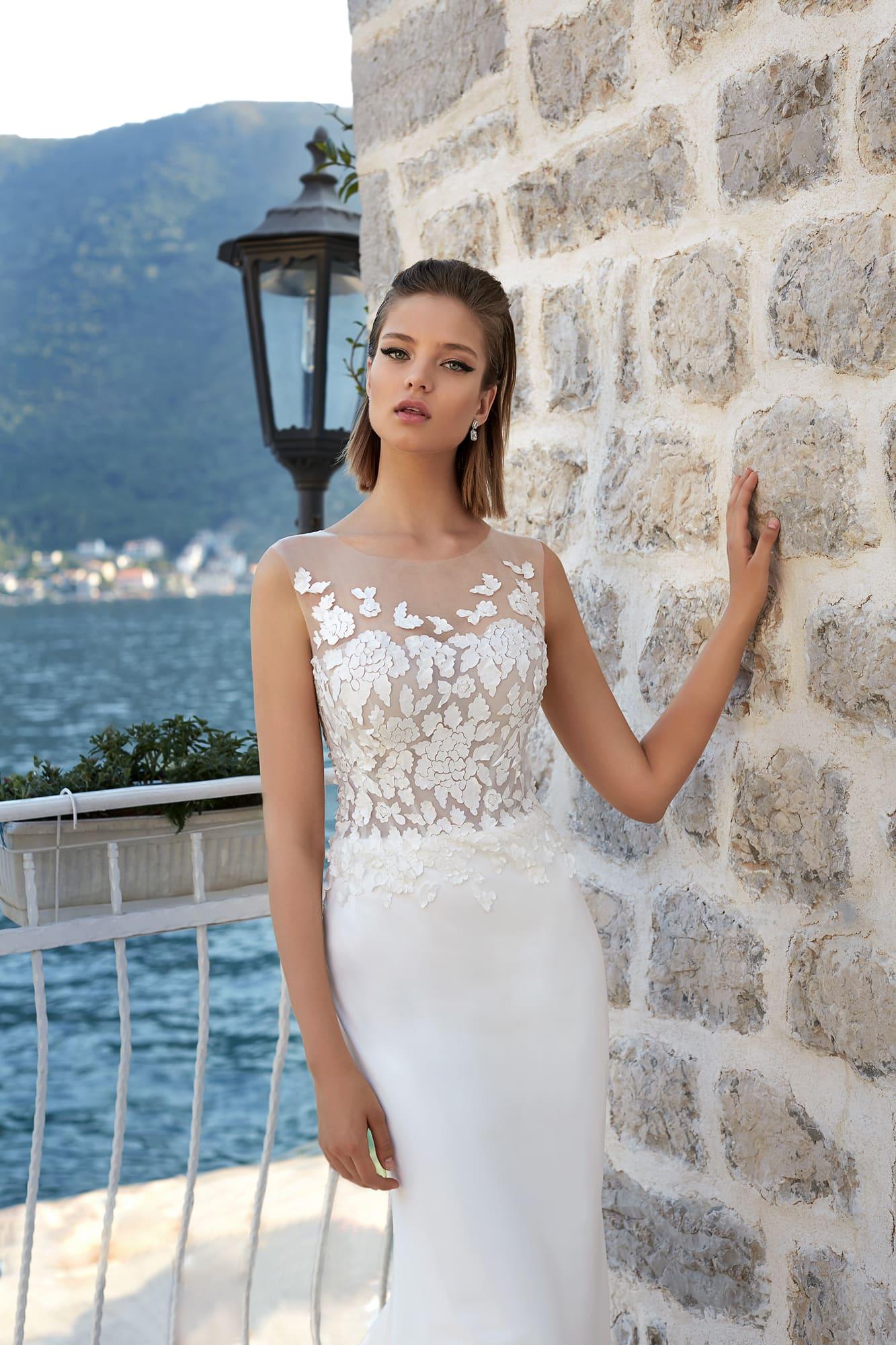 Прямое свадебное платье с эффектным шлейфом и объемной отделкой закрытого лифа.