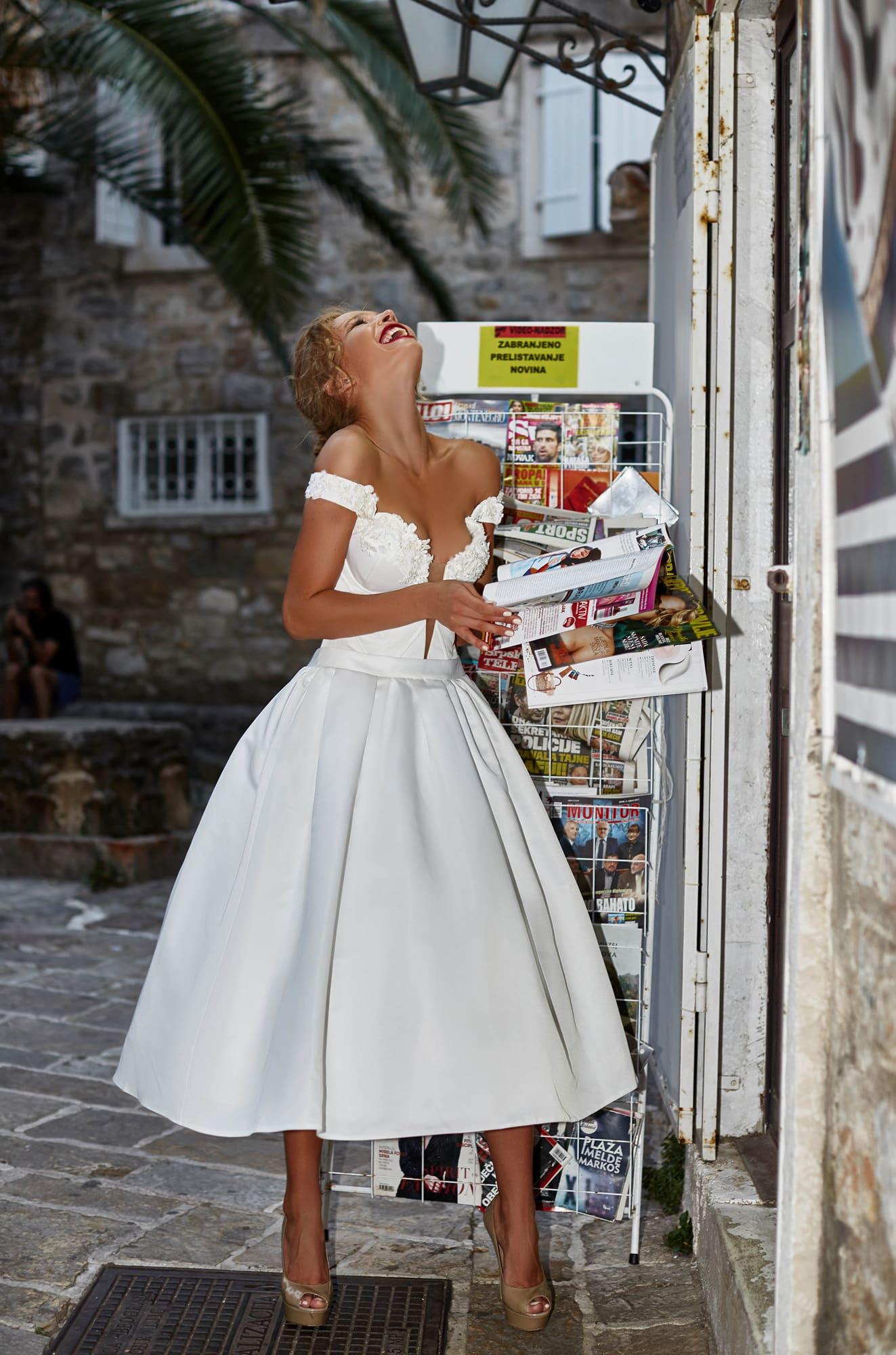 Стильное свадебное платье с пышной юбкой длины миди и притягательным вырезом декольте.