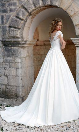 Пышное свадебное платье с атласной юбкой и закрытым лифом, покрытым глянцевым кружевом.