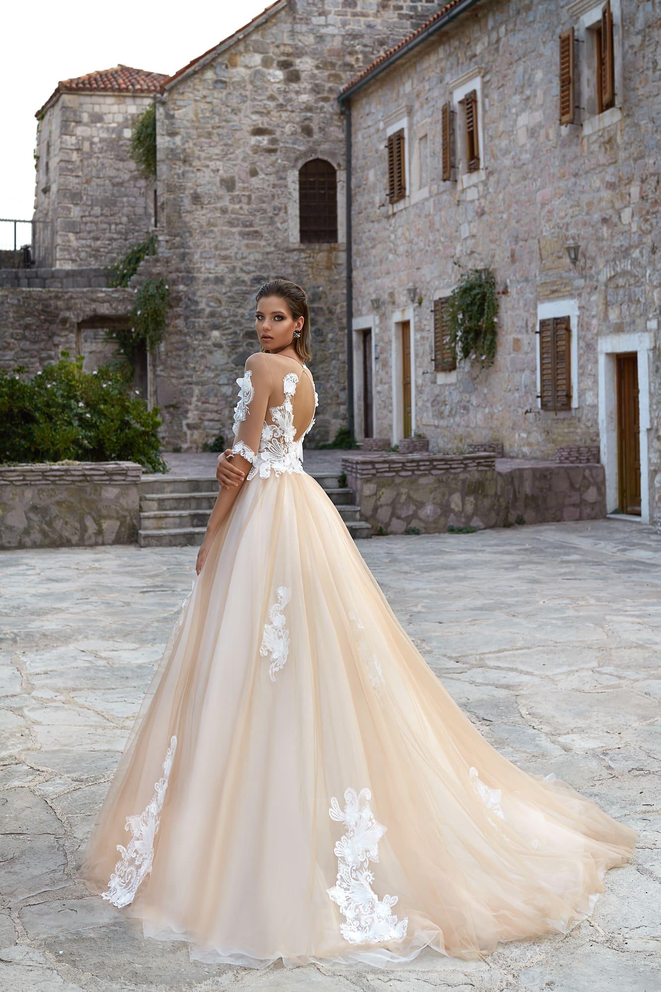 Великолепное свадебное платье с портретным декольте и пышной юбкой кремового цвета.