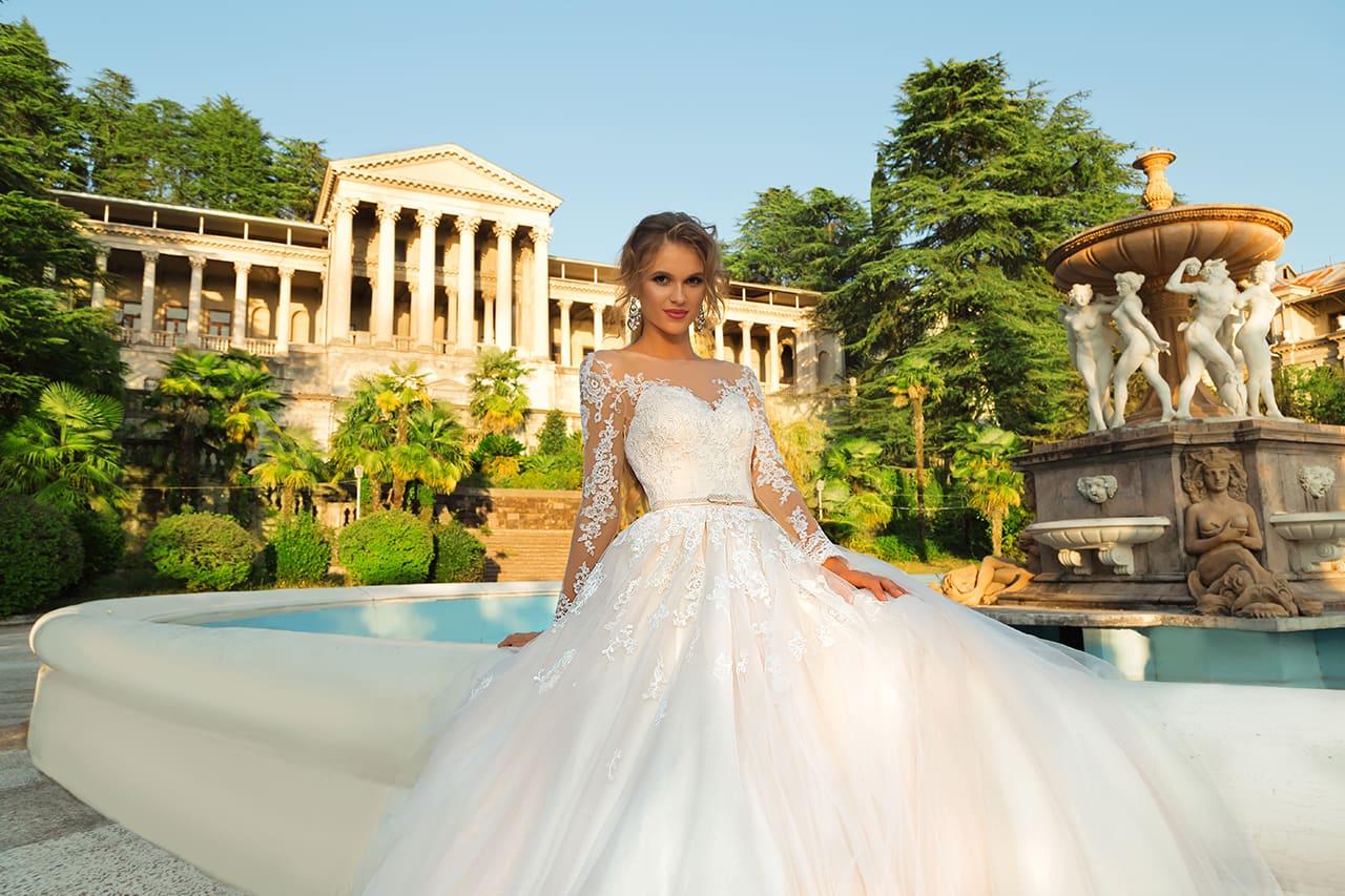 Свадебное платье «принцесса» с длинным прозрачным рукавом и кружевным декором.