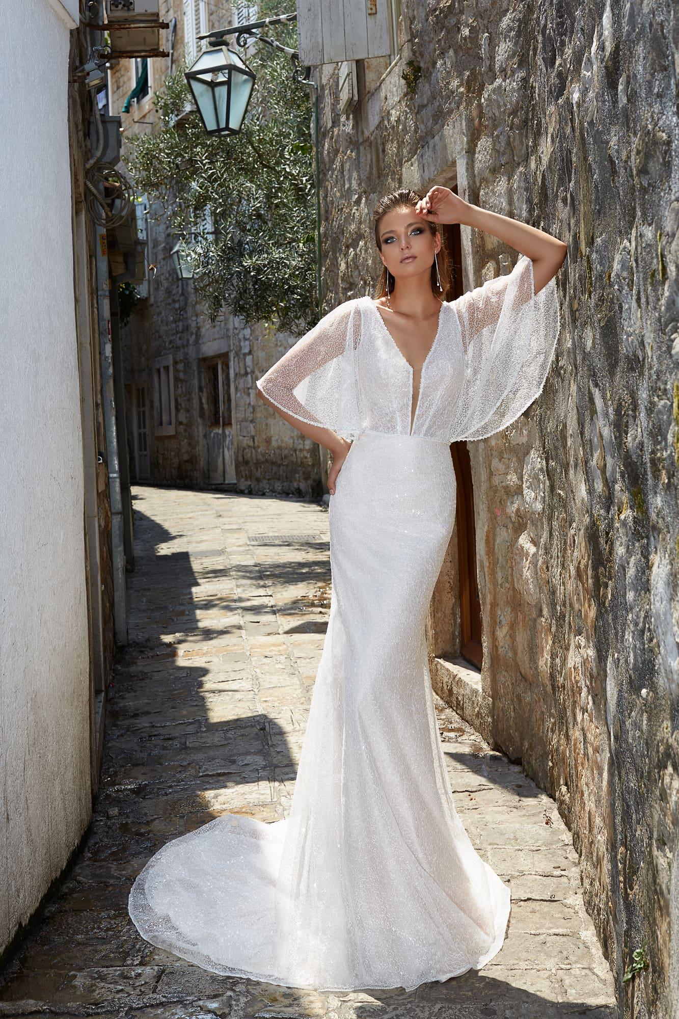 Облегающее силуэт свадебное платье из роскошной сияющей ткани, с эффектным рукавом.