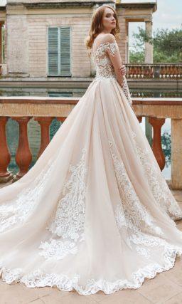 Пышное свадебное платье с фигурным кружевным лифом и длинным прозрачным рукавом.