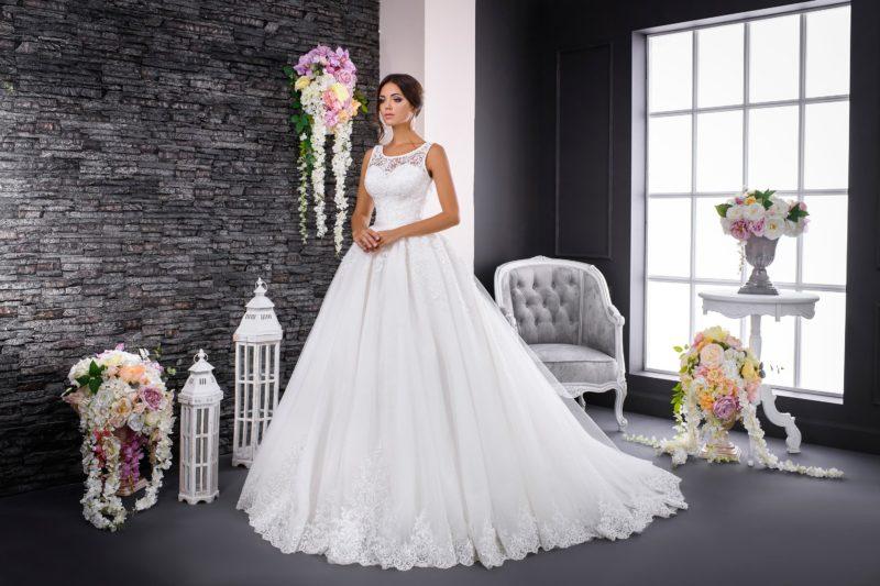 Пышное свадебное платье с изящным округлым вырезом, кружевным декором и шлейфом.