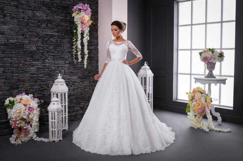 Пышное свадебное платье с элегантным кружевным рукавом и широким поясом на талии.