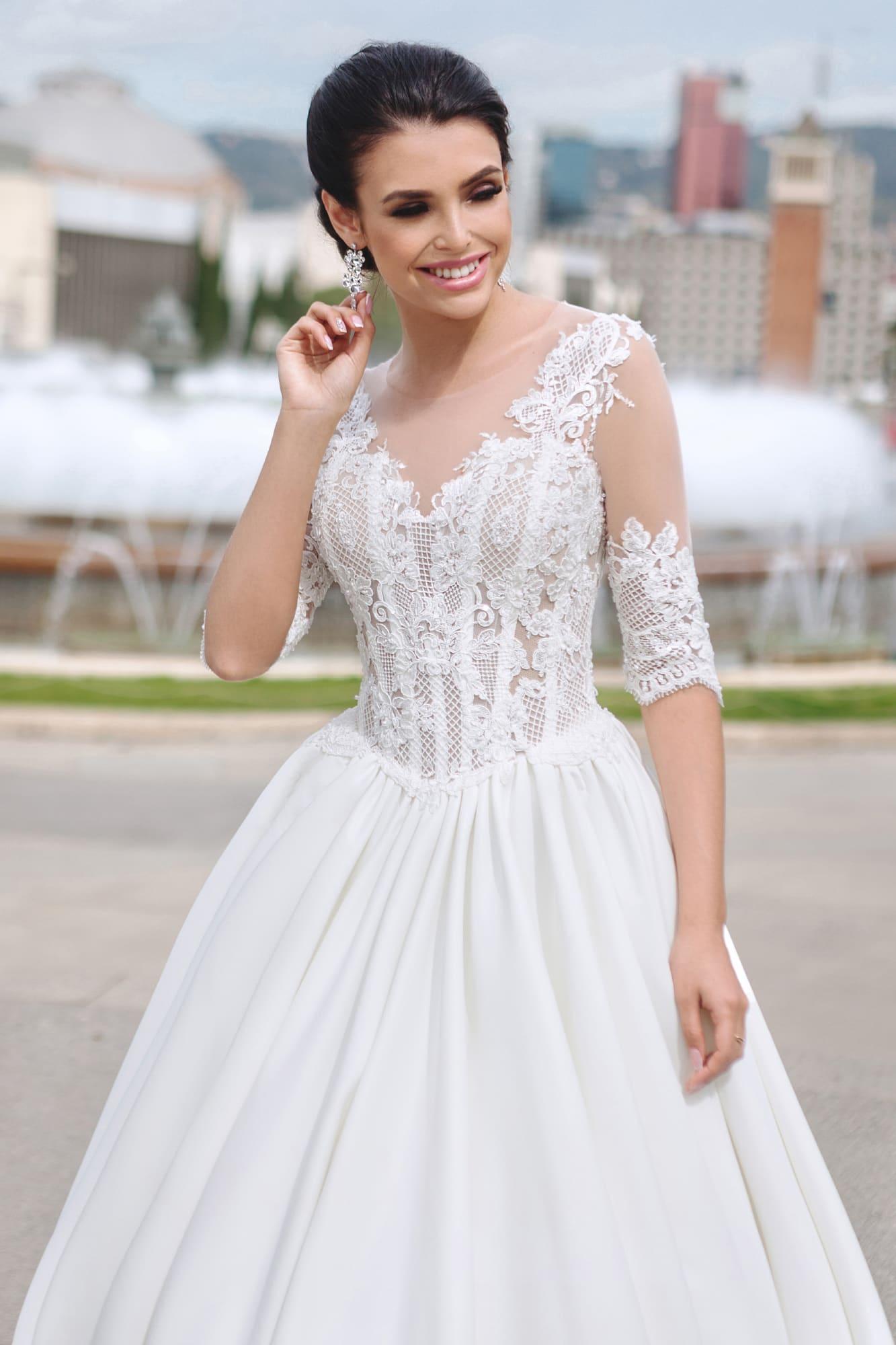 Свадебное платье с полупрозрачным кружевным корсетом и атласной юбкой А-силуэта.