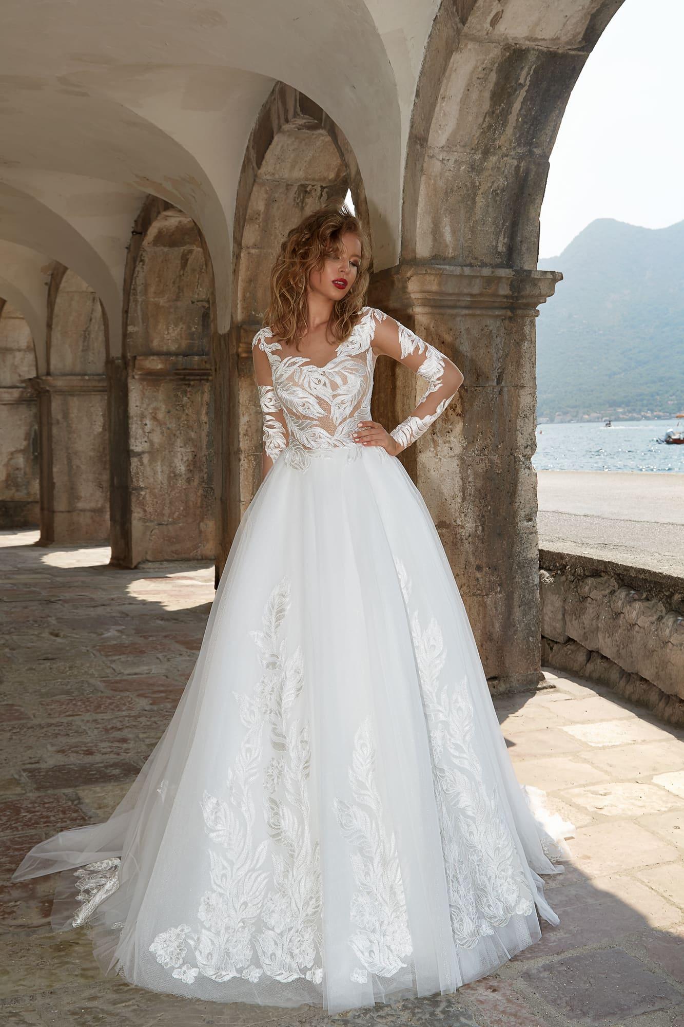 Пышное свадебное платье с полупрозрачными рукавами и эффектным глянцевым декором.