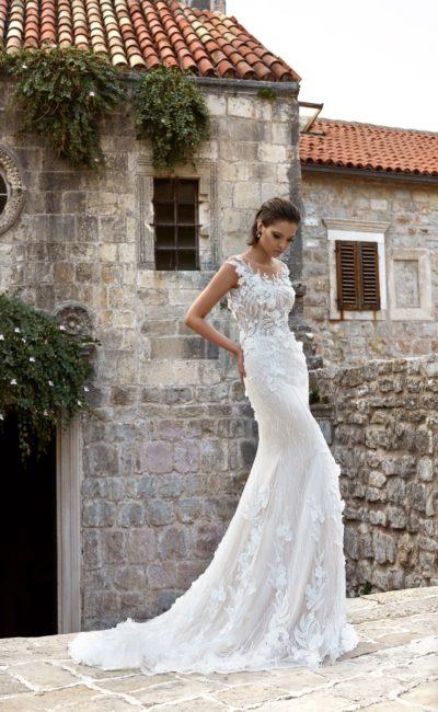 Облегающее свадебное платье с закрытым лифом и нежной объемной отделкой по верху.