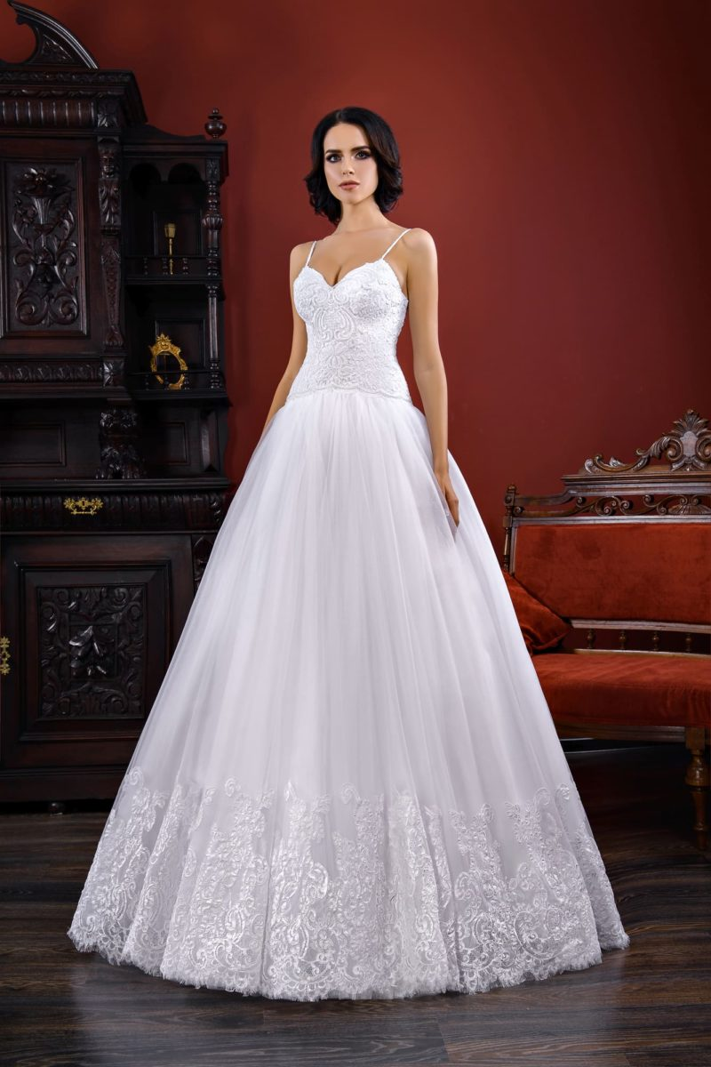 Женственное свадебное платье с заниженной линией талии и узкими бретелями на лифе.