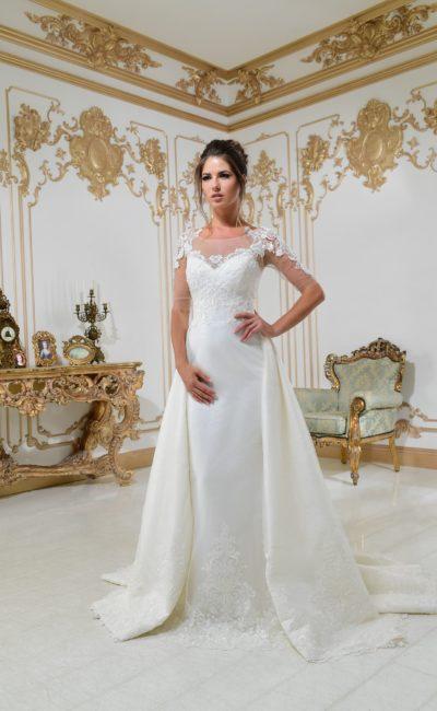 Стильное свадебное платье с эффектной верхней юбкой и длинными полупрозрачными рукавами.
