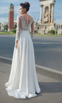 Прямое свадебное платье с длинным полупрозрачным рукавом и отделкой из аппликаций.