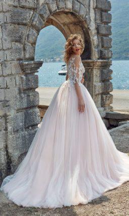 Нежное свадебное платье с полупрозрачным верхом, оформленным кружевом, и розовой юбкой.