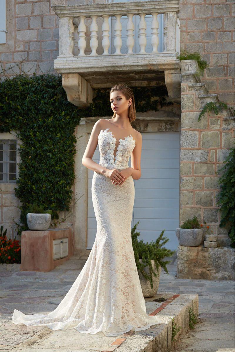 Романтичное свадебное платье с глубоким вырезом и деликатной бежевой подкладкой под кружевом.