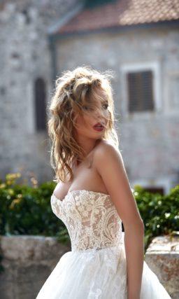 Пышное свадебное платье с открытым лифом, украшенным кружевом, и фактурной юбкой.