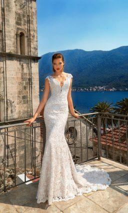 Впечатляющее свадебное платье силуэта «рыбка», выполненная из кружева на бежевой подкладке.
