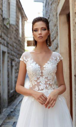 Пышное свадебное платье с полупрозрачным лифом, украшенным кружевными аппликациями.
