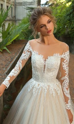 Свадебное платье цвета слоновой кости с эффектной юбкой и кружевным декором верха.