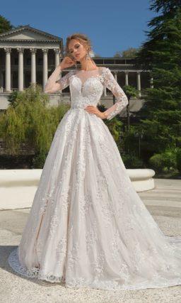 Свадебное платье цвета слоновой кости с пышной юбкой и длинным кружевным рукавом.