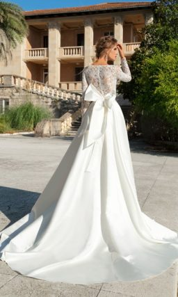 Свадебное платье с длинным кружевным рукавом и эффектным бантом.