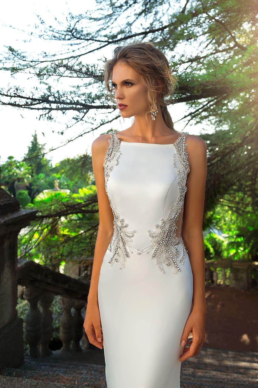 Атласное свадебное платье облегающего кроя, расшитое серебристым бисерным узором.