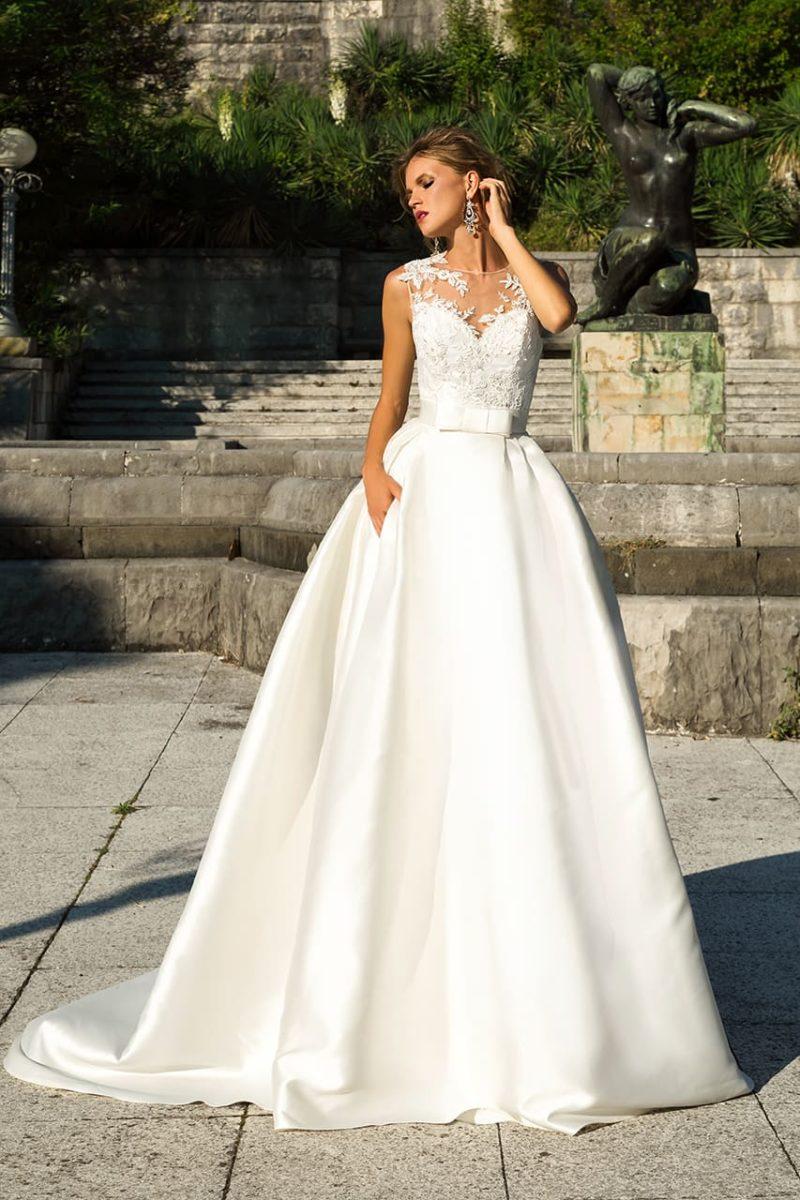 Свадебное платье с роскошной атласной юбкой и кружевным декором над декольте.