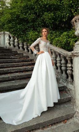 Свадебное платье с атласной юбкой силуэта «принцесса» и иллюзией прозрачности верха.