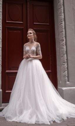 Свадебное платье пышного кроя с кружевным верхом и рукавом длиной до локтя.