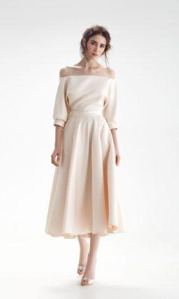 Свадебное платье бежевого цвета с юбкой длины миди и открытым верхом с пышным рукавом.