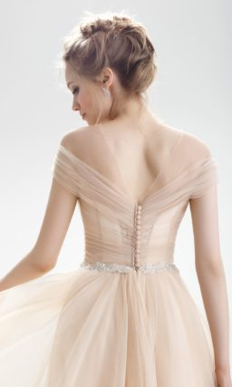 Свадебное платье бежевого цвета с изящным декольте и отделкой драпировками.