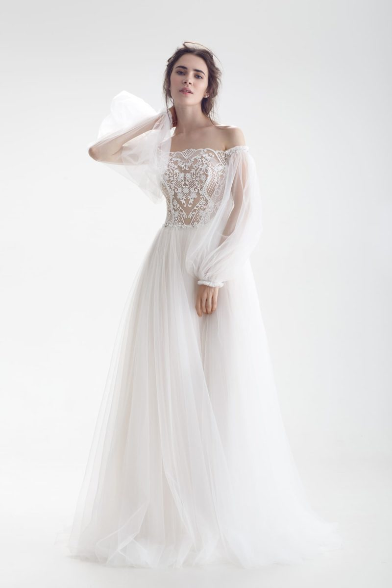 Свадебное платье с пышным прозрачным рукавом и многослойной юбкой.