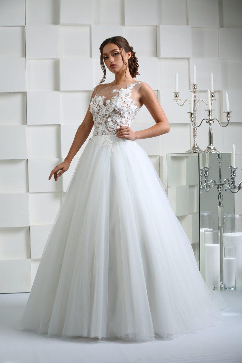 Свадебное платье с полупрозрачным верхом, декорированным кружевными аппликациями.
