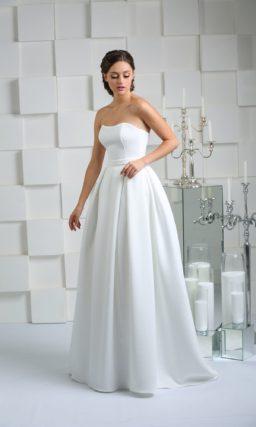Свадебное платье в лаконичном стиле, с открытым лифом и пышной юбкой со складками.