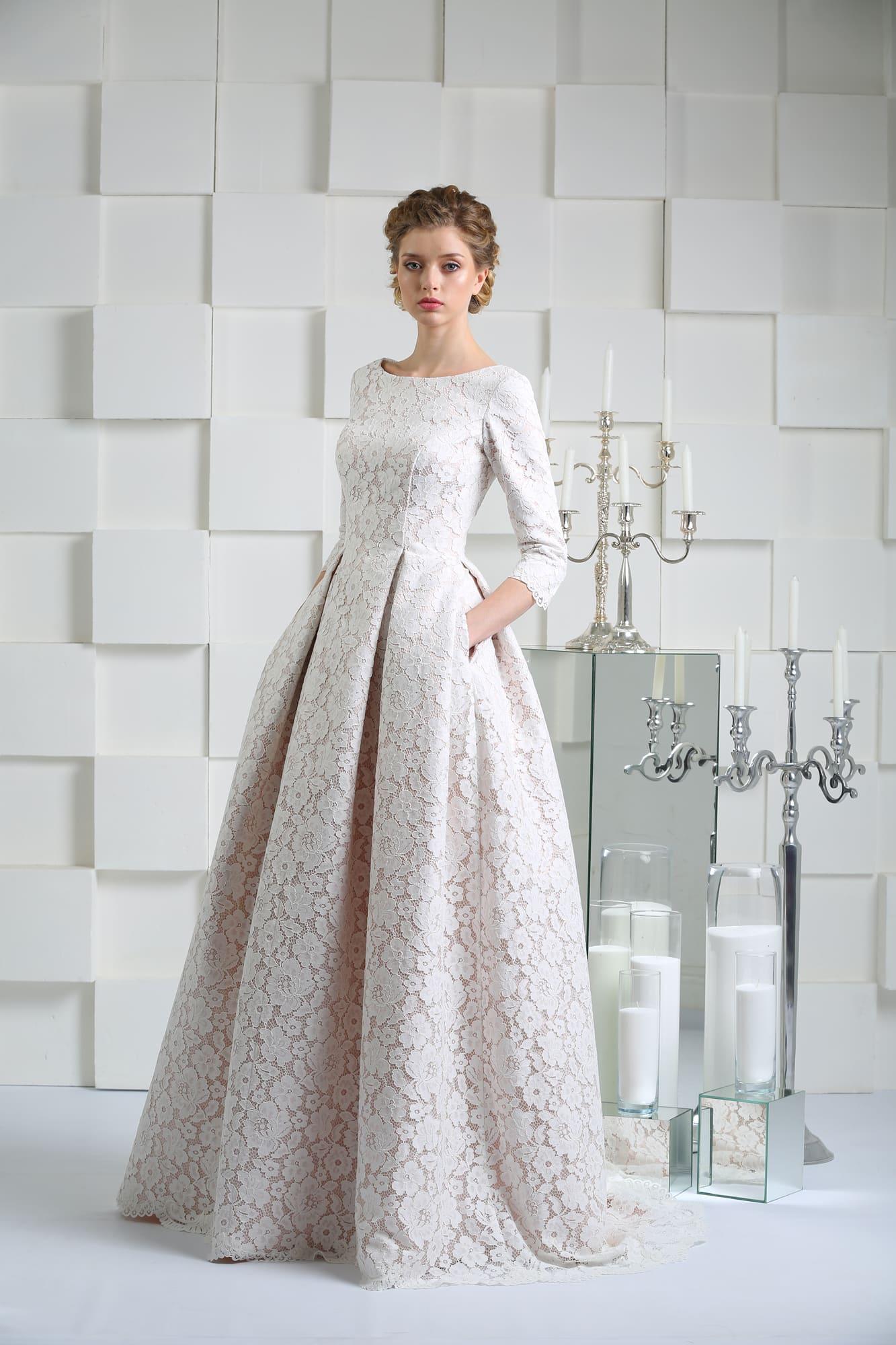 Свадебное платье с длинным рукавом и скрытыми карманами, покрытое кружевом.